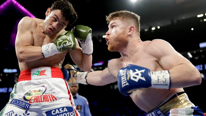 Canelo Alvarez, right, lands a shot to ribs of Julio Cesar Chavez Jr. during their fight in Las Vegas on Saturday night.