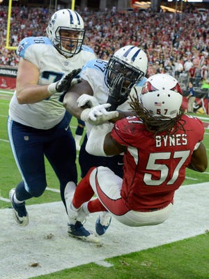 Titans guard Quinton Spain (67) and offensive tackle Jack Conklin (78) knock Cardinals linebacker Josh Bynes (57) out of bounds as he runs back an interception during the second half at University of Phoenix Stadium Sunday, Dec. 10, 2017 in Glendale, Ariz.