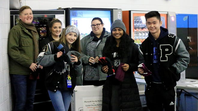 On Dec. 27 at Canton Arctic Edge Arena, hockey fans brought new hats and gloves to donate to Plymouth United Way. Those who did received free admission to the varsity hockey game between Canton and Plymouth. From left are Gavin Vaughan, Hailey Vaughan, Rachel Smith, Randi Williams of United Way, Karishma Nair and Nick Yoshioka.