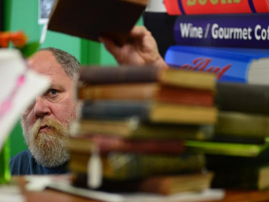 Alix Bernard, one of the owners of the West End bookstore Joe's Place, checks antique books at the West End shop.