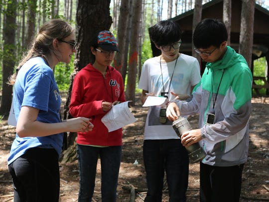 Marshfield High School senior Claire Greenlee, from left, helps Chinese students, Lu Yinghan, Xu Yanheng and Xu Jiaxian as they do some geocaching at the Marshfield School Forest near Lindsey on Friday, July 24.