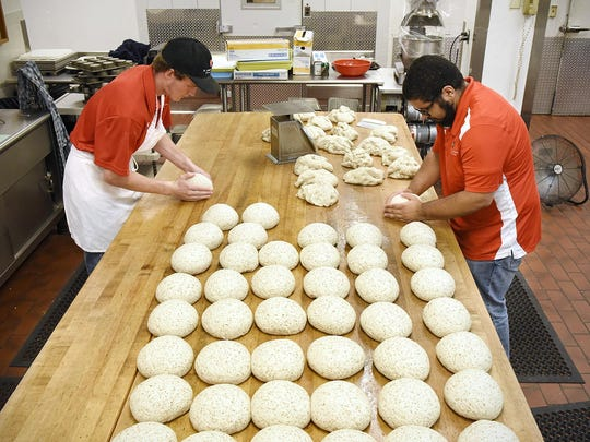 Jared McComber and Rafael Roman form dough into balls that will be rolled and set aside to rise before baking the 60-loaf batch of bread Wednesday at St. John's University.