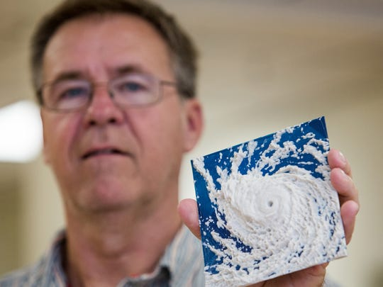 Joe Otto holds up a 3-D print of a hurricane in his 3D printing shop, Sovereign Air.