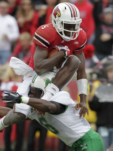 University of Louisville quarterback Teddy Bridgewater (5) jumps over top Marshall University's Phillip Warren (6) for the touchdown during the first half of play at Papa John's Cardinal Stadium in Louisville, Kentucky.    (By John Sommers II,    Special to the Courier-Journal)      October 1, 2011