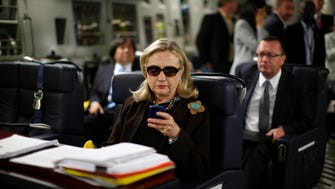 Secretary of State Hillary Rodham Clinton checks her Blackberry from a desk inside a C-17 military plane upon her departure from Malta and en route to Tripoli, Libya, on Oct. 18, 2011.