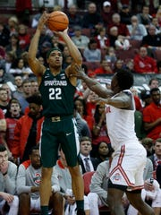 Michigan State guard Miles Bridges, left, goes up to