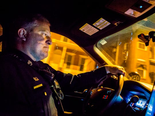 Sgt. Bill Schmid, of the Wilmington Police Department, drives his car through the streets of Wilmington on patrol Sunday night, Dec. 18, 2016.