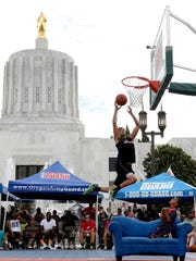 LJ Westbrook, 20, of Salem, jumps over his little brother, Tko Westbrook, 7, and a couch in the slam dunk contest during the Oregon National Guard Hoopla XVII at the Oregon State Capitol in Salem on Saturday, Aug. 8, 2015. Westbrook won the slam dunk contest.