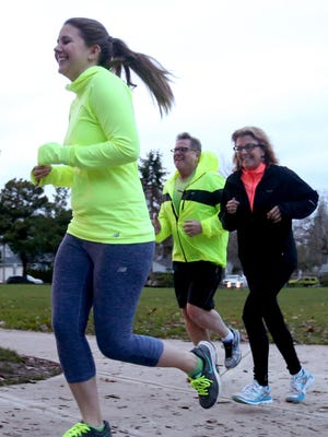 Kathy Eustrom, right, her husband Jim and their daughter Morgan jog together at McKinley Elementary School in Salem on Feb. 23. Kathy started to jog to improve her health and influenced her family in the process.