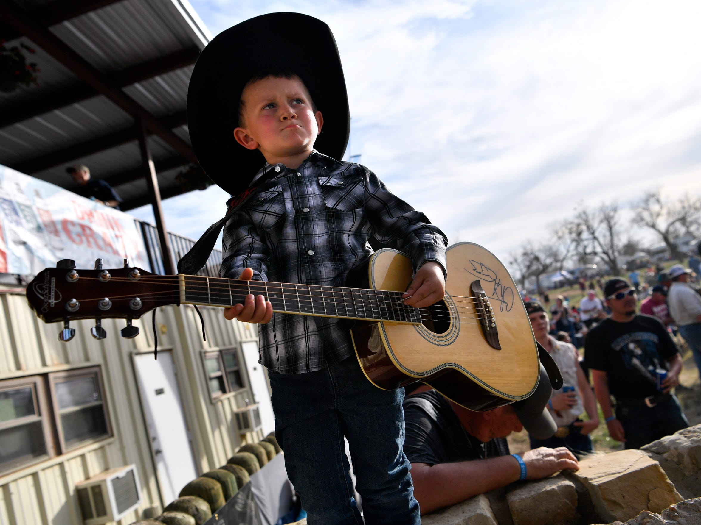 """Bubba Crabtree, then 5, """"performs"""" at the side of the stage in 2018. His guitar is autographed by many of the Outlaws & Legends artists."""