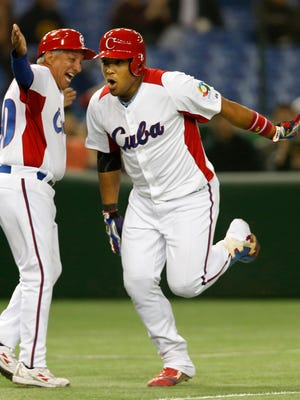 Cuba rightfielder Yasmany Tomas, right, celebrates with third-base coach Primitivo Diaz after hitting a three-run homer off Taiwan pitcher Yang Yao-hsun in the World Baseball Classic on March 9, 2013.