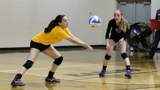 Keeping a volley going for Plymouth Christian during a recent game is libero Divna Roi (left), with Grace Kellogg (No. 3) standing by.