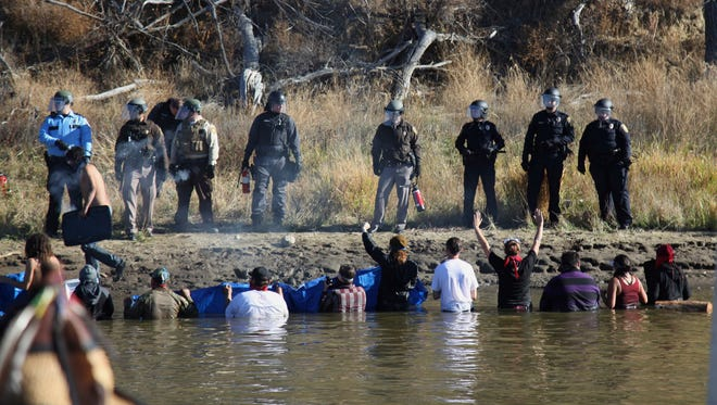 Dozens of protestors demonstrating against the expansion of the Dakota Access Pipeline wade in cold creek waters Nov. 2, 2016, confronting local law enforcement, as remnants of pepper spray waft over the crowd near Cannon Ball, N.D.