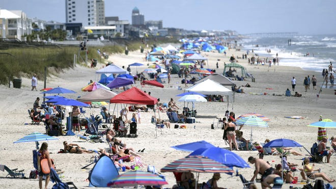 Beachgoers hang out just north of Kure Beach Pier at Kure Beach, N.C., Saturday, May 23, 2020. The town lifted the majority of beach restrictions related to the coronavirus on May 15.