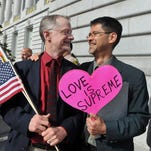 """John Lewis, left, and his husband Stuart Gaffney, plaintiffs in the 2008 Defense of Marriage Act (DOMA) case, hold flags and a sign reading """"Love is Supreme"""" outside City Hall after the U.S. Supreme Court same-sex marriage ruling in San Francisco, California, U.S., on Friday, June 26, 2015. Same-sex couples have a constitutional right to marry nationwide, the U.S. Supreme Court said in a historic ruling that caps the biggest civil rights transformation in a half-century. Photographer: Josh Edelson/Bloomberg *** Local Caption *** John Lewis; Stuart Gaffney ORG XMIT: 561863321"""