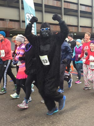 A person dressed as a gorilla raises his or her arms as the First Run 5K begins on Cherry Street in Burlington on Sunday, Jan. 1, 2017.