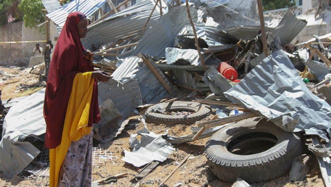 A woman stands next to rubble caused by explosion in Mogadishu, Somalia, May 17, 2017.