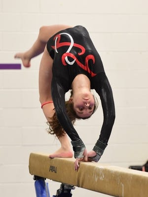 Livonia Red's Olivia Dillon is pictured competing on the balance beam.