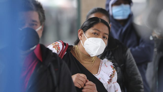 Passengers wearing protective face masks as a precaution against the spread of the new coronavirus, wait in a bus line, in Quito, Ecuador, Wednesday, June 3, 2020. After 80 days of an almost complete shutdown, the capital city lowers its warning alert from red to yellow allowing for the freer movement of people and the opening of many businesses.
