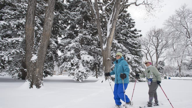 Georgia Locker and Marty Tharp take advantage of snowfall to snowshoe in City Park on March 18, 2016.
