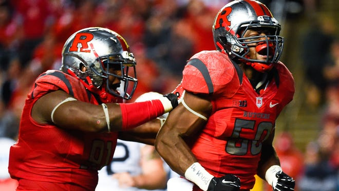 Quentin Gause, right, of the Rutgers Scarlet Knights celebrates with teammate Darius Hamilton after a play during a game against the Penn State.