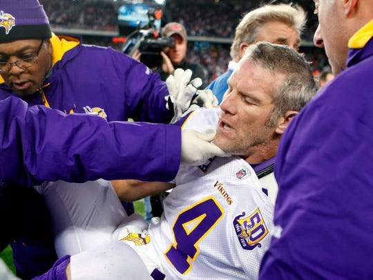 "In this 2010, file photo, Minnesota Vikings quarterback Brett Favre, center, is helped onto a cart to be taken off the field after a hit from New England Patriots' Myron Pryor during a game in Foxborough, Mass. Favre has said he might have suffered ""thousands"" of concussions during his Hall of Fame career."