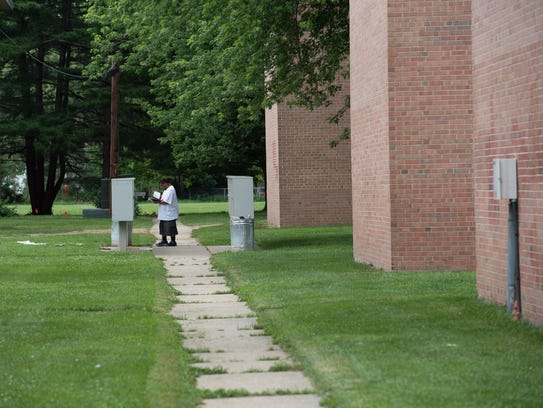 A resident reads through his mail at Alder Park Apartments