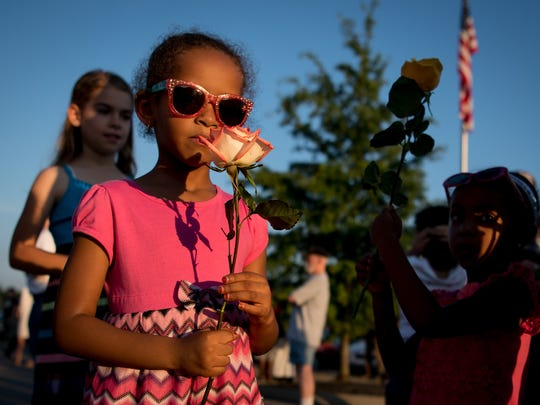 Manar Omer, 5, holds a flower during a vigil at the Islamic Center of Murfreesboro in Murfreesboro, Tenn., Tuesday, July 11, 2017. The vigil was in response to a recent incident of vandalism at the center.
