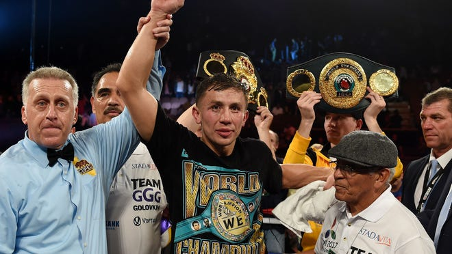 Boxer Gennady Golovkin from Kazakhstan (C) celebrates after knocking out Willie Monroe Jr. of the US in the sixth round during their Middleweight World Championship bout at the Forum Arena.