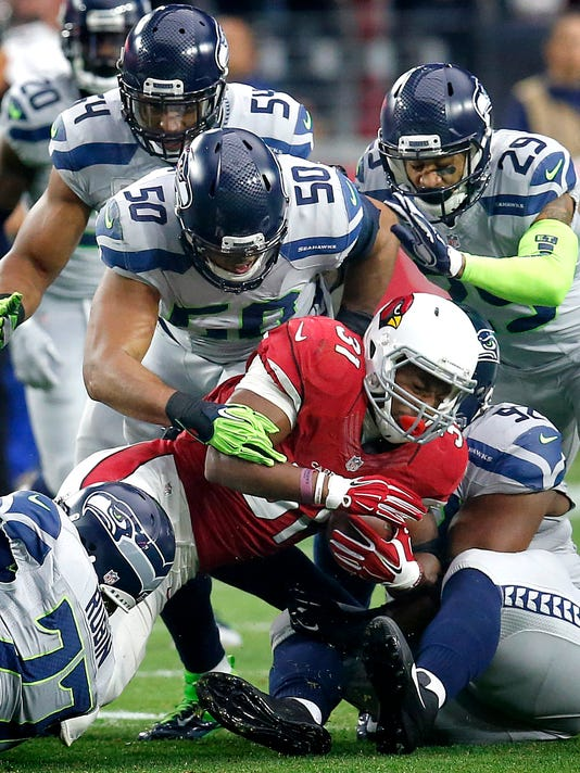 Arizona Cardinals running back David Johnson (31) is stopped by Seattle Seahawks outside linebacker K.J. Wright (50), free safety Earl Thomas (29), defensive tackle Ahtyba Rubin (77), defensive tackle Brandon Mebane (92) and  middle linebacker Bobby Wagner (54) during the first half of an NFL football game, Sunday, Jan. 3, 2016, in Glendale, Ariz. (AP Photo/Rick Scuteri)