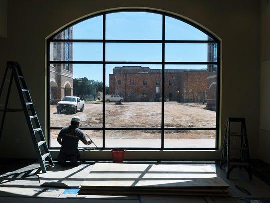 Jaimie Ochoa of SilvaFox cleans windows in a lounge
