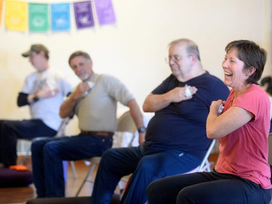 Amy Olson jokes with others in the Yoga for Veterans yoga class at the Yoga for Wellness studio. Olson said yoga has improved her balance and stability and alleviates pain from a foot injury.
