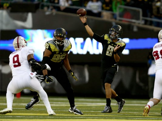 Oregon quarterback Marcus Mariota (8) throws the ball during the first quarter against Stanford in an NCAA college football game in Eugene, Ore., Saturday, Nov. 1, 2014. (AP Photo/Ryan Kang)
