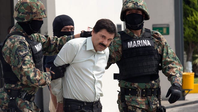 "Drug trafficker Joaquin ""El Chapo"" Guzman is escorted to a helicopter by Mexican security forces at Mexico's International Airport in Mexico City on Feb. 22, 2014."