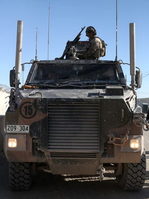 A U.S. solider sits atop a MRAP in Kandahar, Afghanistan, Sunday, Dec. 8, 2013.