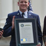 Spencer Stone holds an award honoring him and his friends Anthony Sadler and Alek Skarlatos for helping to stop a terrorist plot aboard a Paris-bound train.