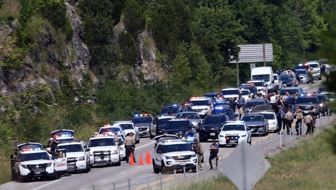 Police cars gather at the scene of a standoff on Interstate 55 near Highway 61 on Monday, July 24, 2017, in Jefferson County Mo. Authorities say a carjacking suspect died  after a shootout with police on a busy stretch of interstate near St. Louis.