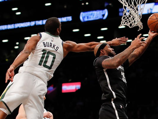 Brooklyn Nets forward Trevor Booker (35) shoots next to Utah Jazz guard Alec Burks (10) during the second quarter of an NBA basketball game, Friday, Nov. 17, 2017, in New York. (AP Photo/Julie Jacobson)