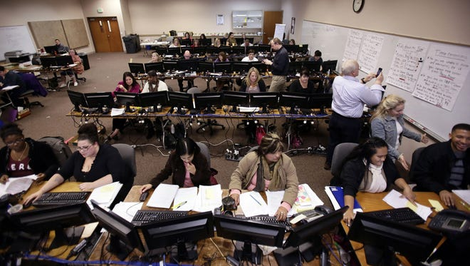 In this Nov. 18, 2013, file photo, a roomful of people work to process applications for Cover Oregon, the state's health exchange program, in Keizer, Ore.
