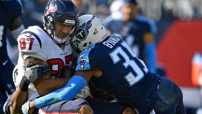 Texans tight end C.J. Fiedorowicz (87) is tackled by Titans safety Kevin Byard (31) in the first half Sunday.