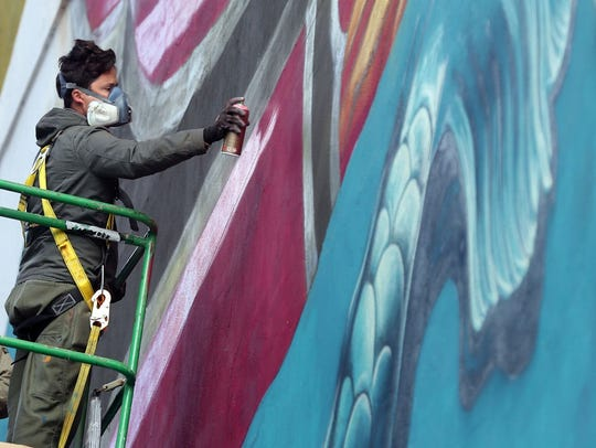 Beau Stanton paints a mural on 5th Avenue North as