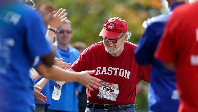 Charles Weydt of Woodruff, Wis., is offered congratulations as he nears the finish as the last one off the course during the Community First Fox Cities Marathon at Riverside Park in Neenah, Wis., Sunday, Sept. 20, 2015. Charles competed in the half marathon competitive walk division.