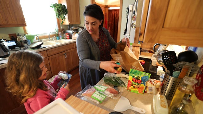 Gabrielle Radford talks to her granddaughter, Rya Radford, 7, while preparing dinner at their Freedom  home. Gabrielle and her partner, Jody Stuck, have had Rya in their care since she was an infant and adopted her when she was 2 years old.