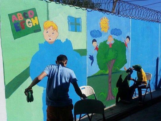 A student paints a mural last month at Centro de Oportunidad,