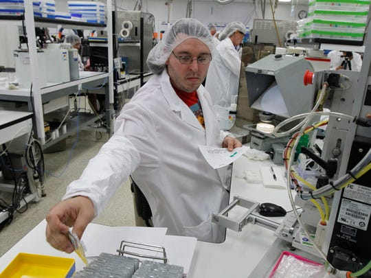 Walter Briggs II stacks a freshly sealed bubble pack after inspecting the set of contact lenses it contains at the CooperVision manufacturing facility in Scottsville.