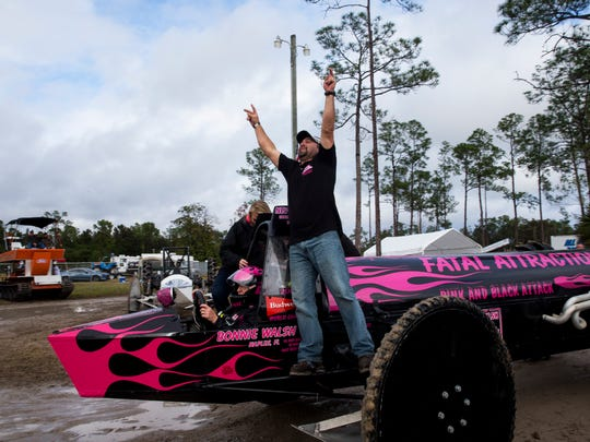 Fatal Attraction crew chief Brett Jameson points to the sky in jubilation as his driver, Bonnie Walsh, drives to the winner's circle during the Budweiser Winter Classic swamp buggy races at Florida Sports Park in Naples, Fla., on Sunday, Jan. 29, 2017. Walsh, who won the Big Feature, was racing for the first time since her husband and buggy partner, Terry, died in March 2016.