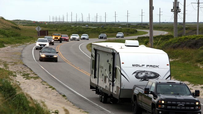 Vacationers head north on NC 12 on Hatteras Island, N.C., on Friday, July 28, 2017.  An estimated 10,000 tourists face a noon deadline Friday for evacuating the island on North Carolina's Outer Banks after a construction company caused a power outage, leaving people searching for a place to eat, stay cool or to resume interrupted vacations.