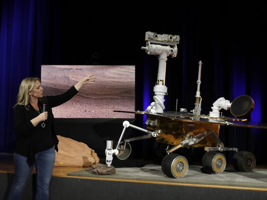 Mars 2020 project system engineer Jennifer Trosper, left, points to a replica of the Mars Exploration Rover Opportunity during a mission briefing at NASA's Jet Propulsion Laboratory Wednesday, Feb. 13, 2019, in Pasadena, Calif. (AP Photo/Marcio Jose Sanchez)