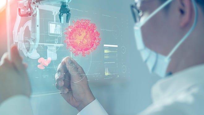 A scientist looking at a digital rendering of a coronavirus.