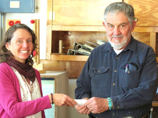 2015 Grant County Art Guild president Tom Vaughn presents a check for additional art supplies to Guadalupe Montessori School art teacher Amy Duncan.